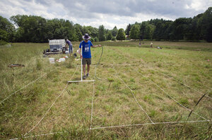 Abraham Noe-Hays, research director of the Rich Earth Institute in Vermont, applies urine to a 5-by-5-meter test plot on a hay farm.