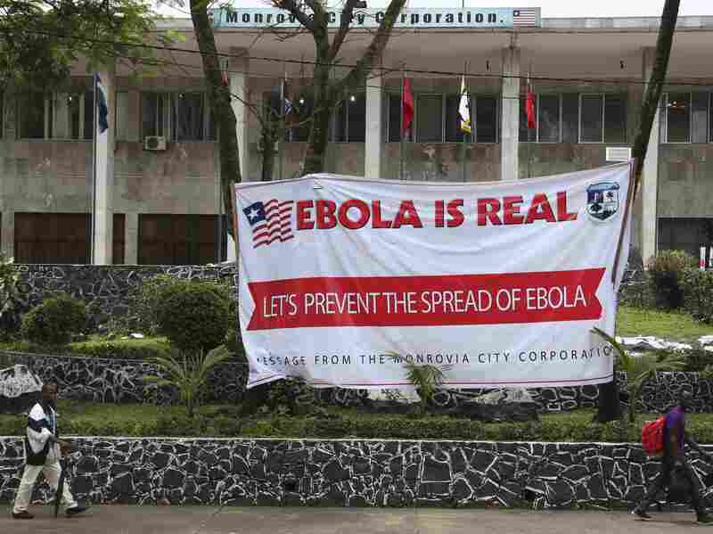 Liberian men walk past an Ebola banner at the Monrovia City Hall in Liberia on Thursday.