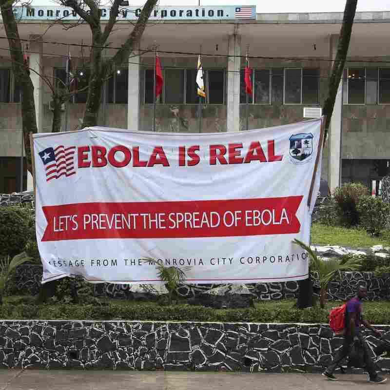 Liberian men walk past an Ebola banner at the Monrovia City Hall in Liberia on Thursday.