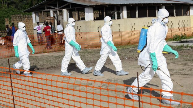Health workers prepare to bury a woman who died of the Ebola in Foya, Liberia, in July.