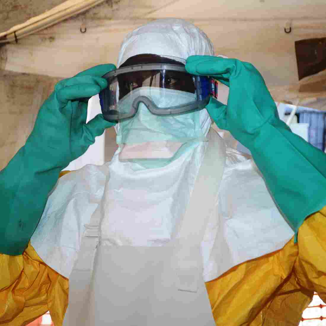 A member of Doctors Without Borders dons protective gear in Conakry, Guinea. U.S. health care workers will use similar protective garb.
