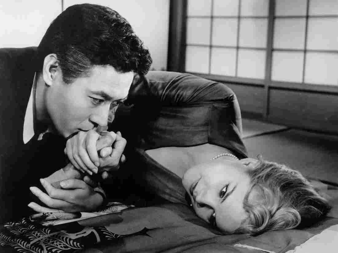 Hidenari Terasaki (James Shigeta) kisses the hand of his wife, Gwen (Carroll Baker), in the 1961 film Bridge to the Sun.