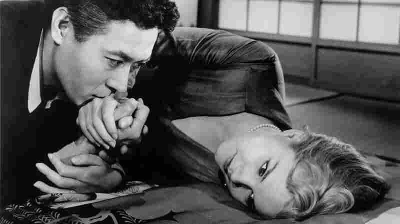 Hidenari Terasaki (James Shigeta) kisses the hand of his wife, Gwen (Carroll Baker), in the 1961 film Bridge to the Sun.