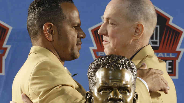 Hall of Fame inductee Andre Reed, left, and former Buffalo Bills quarterback Jim Kelly hug during the Pro Football Hall of Fame enshrinement ceremony Saturday.