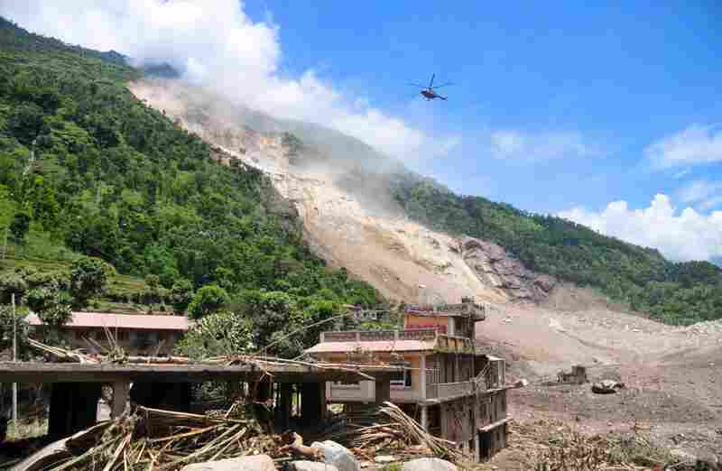 A Nepalese Army helicopter flies over the site of a landslide during a rescue operation in Sindhupalchowk area, about 75 miles east of Katmandu, Nepal on Saturday.