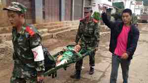 Rescuers carry an injured child on a stretcher after a 6.1 magnitude earthquake hit the area in southwest China's Yunnan province. The quake reportedly collapsed thousands of buildings when it struck Sunday afternoon.