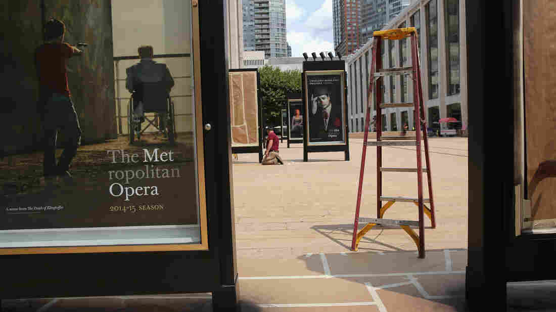 A worker unveils advertisement for future productions at the Metropolitan Opera at Lincoln Center in New York City. The Metropolitan Opera's general manager Peter Gelb has threatened a lockout if there is no an agreement with unions to that represent musicians, stagehands and other employees.