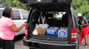 Aundrea Simmons stands next to her minivan with cases of bottled water she bought after Toledo warned residents not to use its water Saturday.