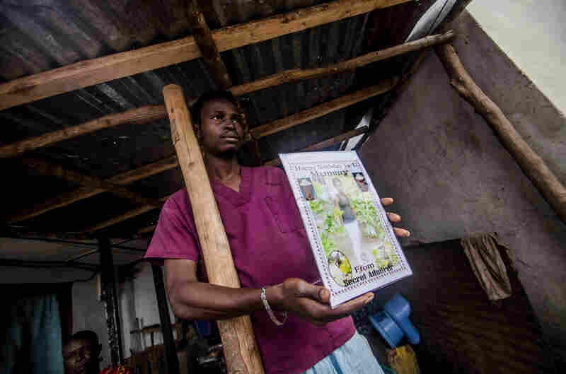 Sule Koroma displays a photo of his sister taken days before she died of Ebola.