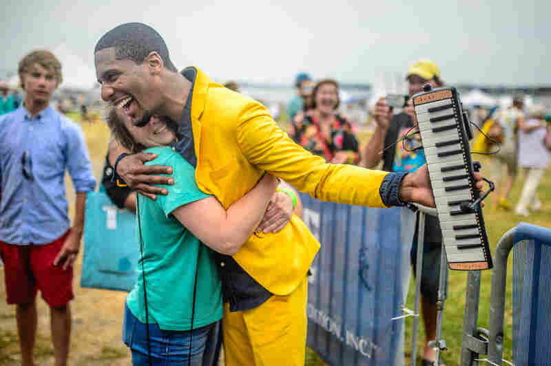 Jon Batiste embraces the crowd at the 2014 Newport Jazz Festival.