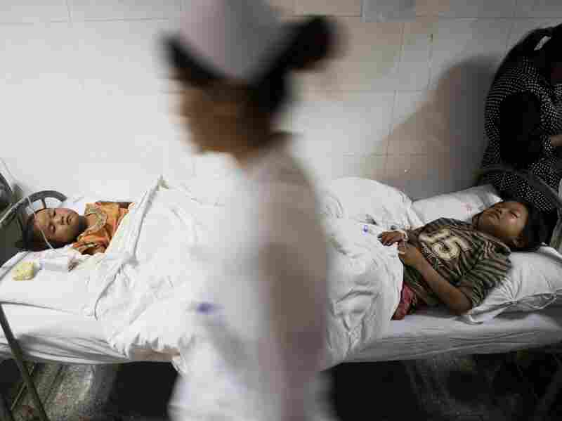 A nurse walks past two injuried children in a hospital corridor on Sunday, during the first night after the earthquake hit.