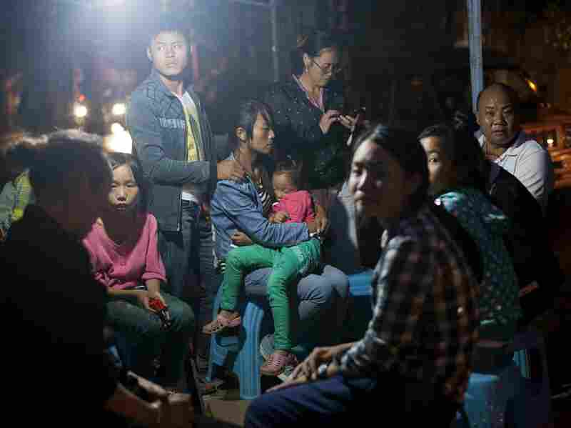 Earthquake victims sit by the street at night. The region was hit by a severe earthquake in 2012.