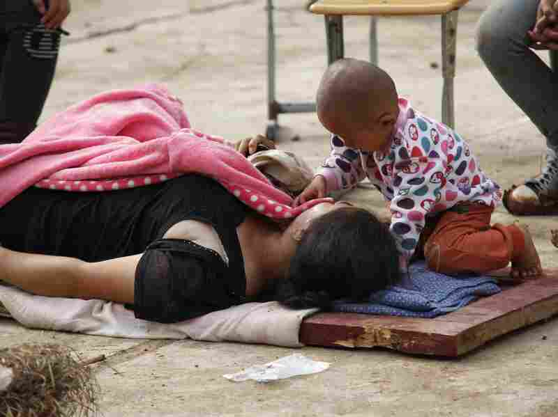 A child touches his injured mother as she lies on a wooden board in Ludian county.