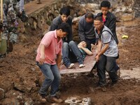 People carry an injured man through the debris in Ludian county in Zhaotong, a city in southwest China's Yunnan province on Monday.