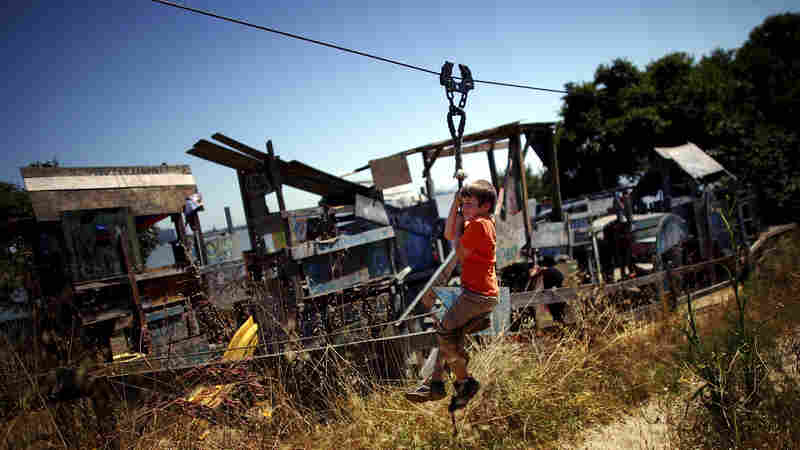 """Joseph Straus, 6, rides a zip line at the Berkeley Adventure Playground, where kids can """"play wild"""" in a half-acre park that has a junkyard feel."""