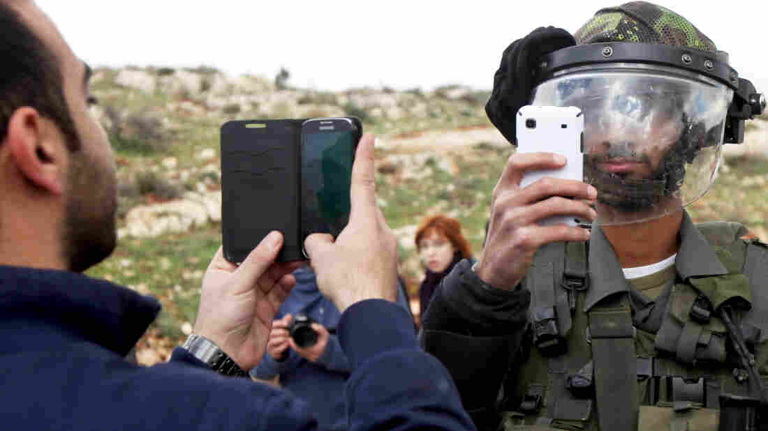 A Palestinian man and a member of the Israeli security forces take pictures of each other with th