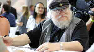 Game of Thrones author George R.R. Martin signs autographs during the 2014 Comic-Con International Convention at the San Diego Convention Center.