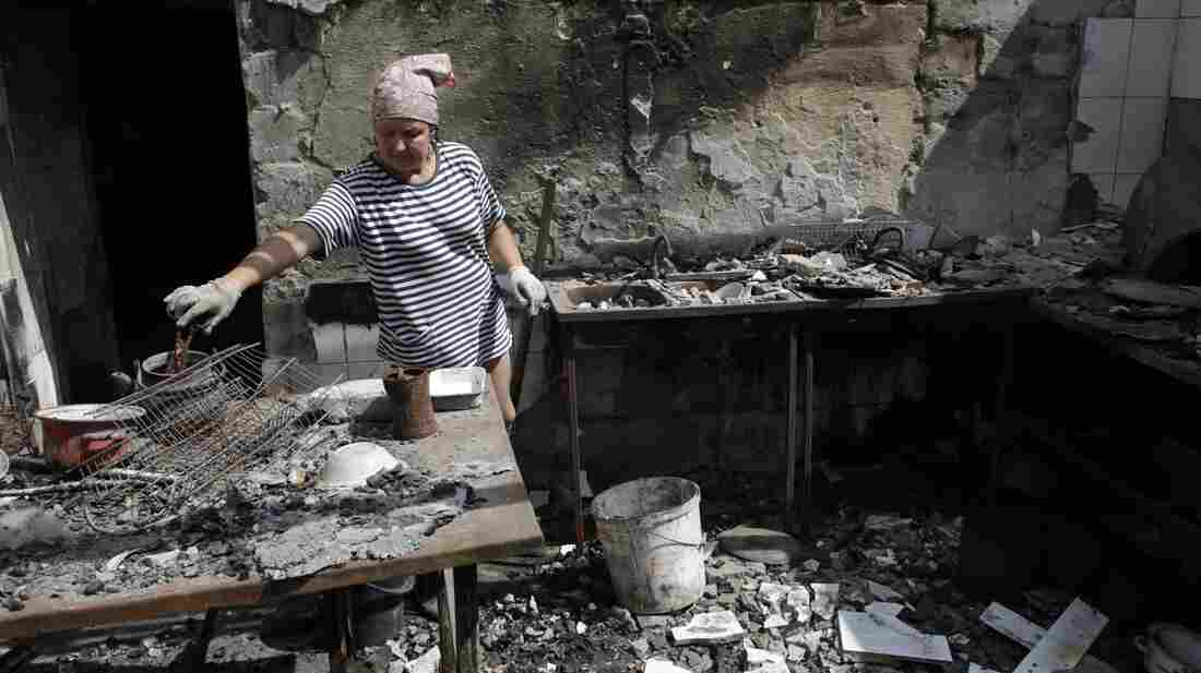 A woman removes debris from a cafe that was destroyed during fighting between Ukrainian forces and pro-Russian militants Aug. 5 in the eastern Ukrainian city of Slavyansk, in the r