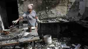 A woman removes debris from a cafe that was destroyed during fighting between Ukrainian forces and pro-Russian militants Aug. 5 in the eastern Ukrainian city of Slavyansk, in the region of Donetsk.