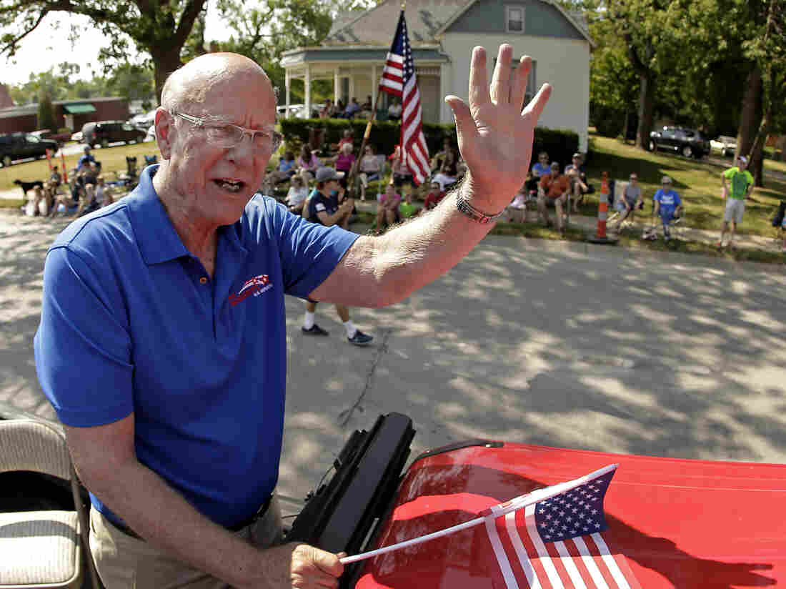 U.S. Sen. Pat Roberts waves to the crowd as he rides on the back of a pickup in a parade Saturday in Gardner, Kan.