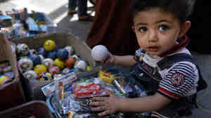 A Palestinian child goes through toys Wednesday at a vendor's stall in a market in Gaza City.