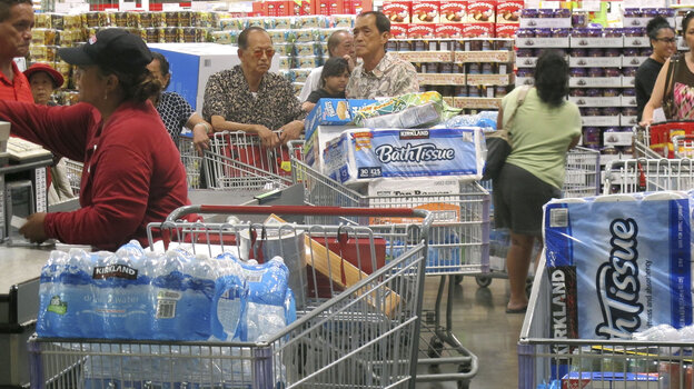 Shoppers stock up on cases of bottled water and other supplies Tuesday in preparation for a hurricane and tropical storm heading toward Hawaii at the Iwilei Costco in Honolulu.