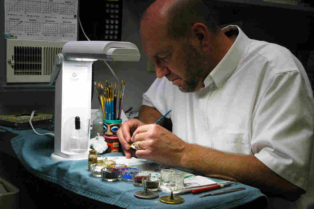 Eric Jahrling adds tiny red threads to a prosthetic eye to represent blood vessels.