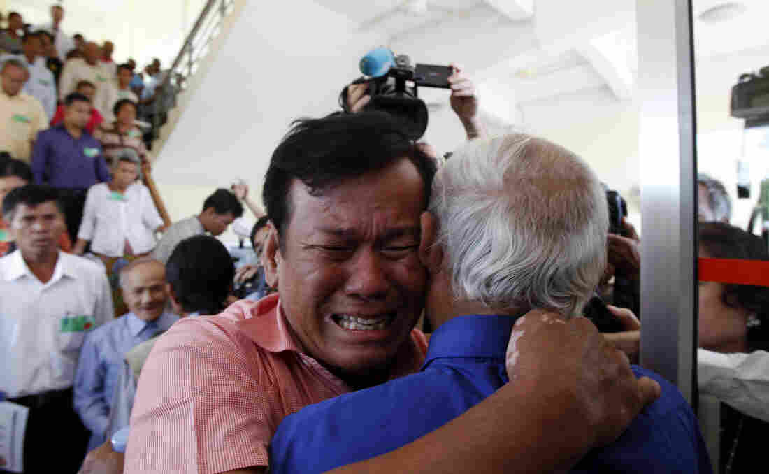 Soum Rithy (center left), who lost family members during the Khmer Rouge regime, and Chum Mey, a survivor of the notorious Tuol Sleng prison, embrace after the verdicts were announced Thursday in Phnom Penh, Cambodia.