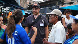 Dave Ohlson speaks with potential patients in a market in Iquitos, Peru.
