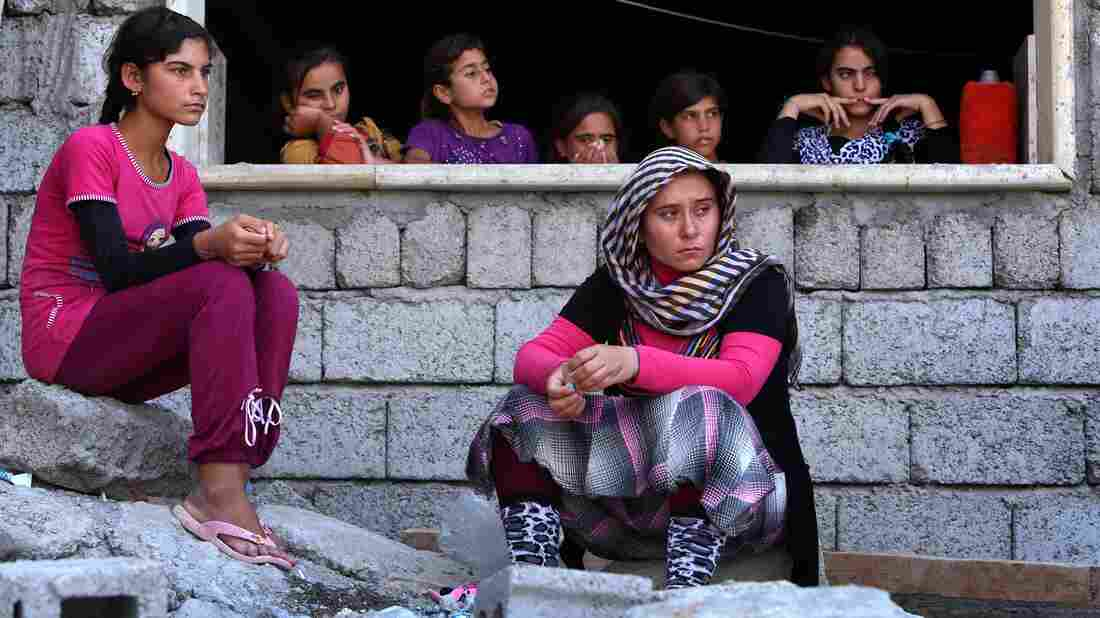 Iraqis from the Yazidi religious sect were driven from their homes in the northern town of Sinjar by the radical Islamic State. These women found safety in the Kurdish city of Dohuk, but others are trapped in barren mountains and face extremely harsh conditions.
