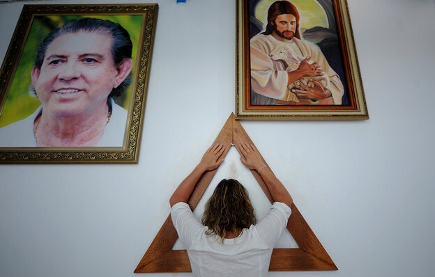 A woman prays on the Sacred Triangle of prayer, with corners representing faith, love and charity, at the House of Saint Ignatius Loyola in Abadiania, Brazil. It was founded by John of God, a popular Spiritist faith healer. Millions of Brazilians practice Spiritism, a religion that incorporates Christian faith and belief in things like reincarnation, psychic mediums and faith healing.