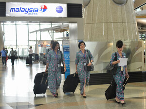 Flight attendants of Malaysia Airlines walk past their company's counter Friday at the Kuala Lumpur International Airport in Malaysia.