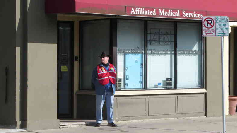 A volunteer escort waits outside a clinic that provides abortions in Milwaukee. Wisconsin is one of many states that have passed laws requiring doctors to have hospital privileges if they perform abortions.