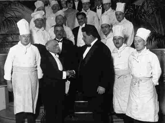 """Chef Georges-Auguste Escoffier (in the foreground on the left), who invented the culinary """"brigade system,"""" photographed with French Prime Minister Edouard Herrio in 1928."""