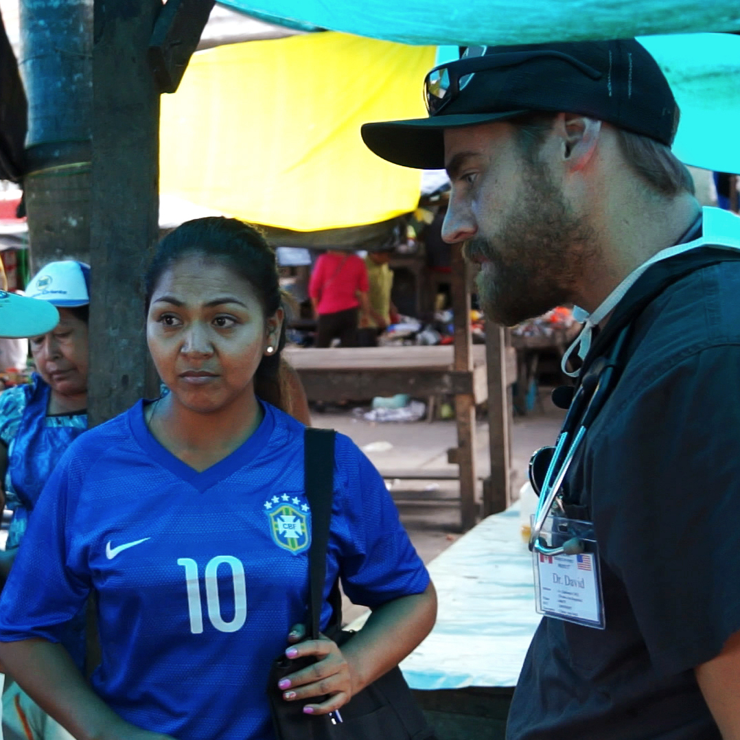 Medical student Dave Ohlson and Leovina, a local counselor, talk with potential patients in Belen, a neighborhood in Iquitos, Peru.