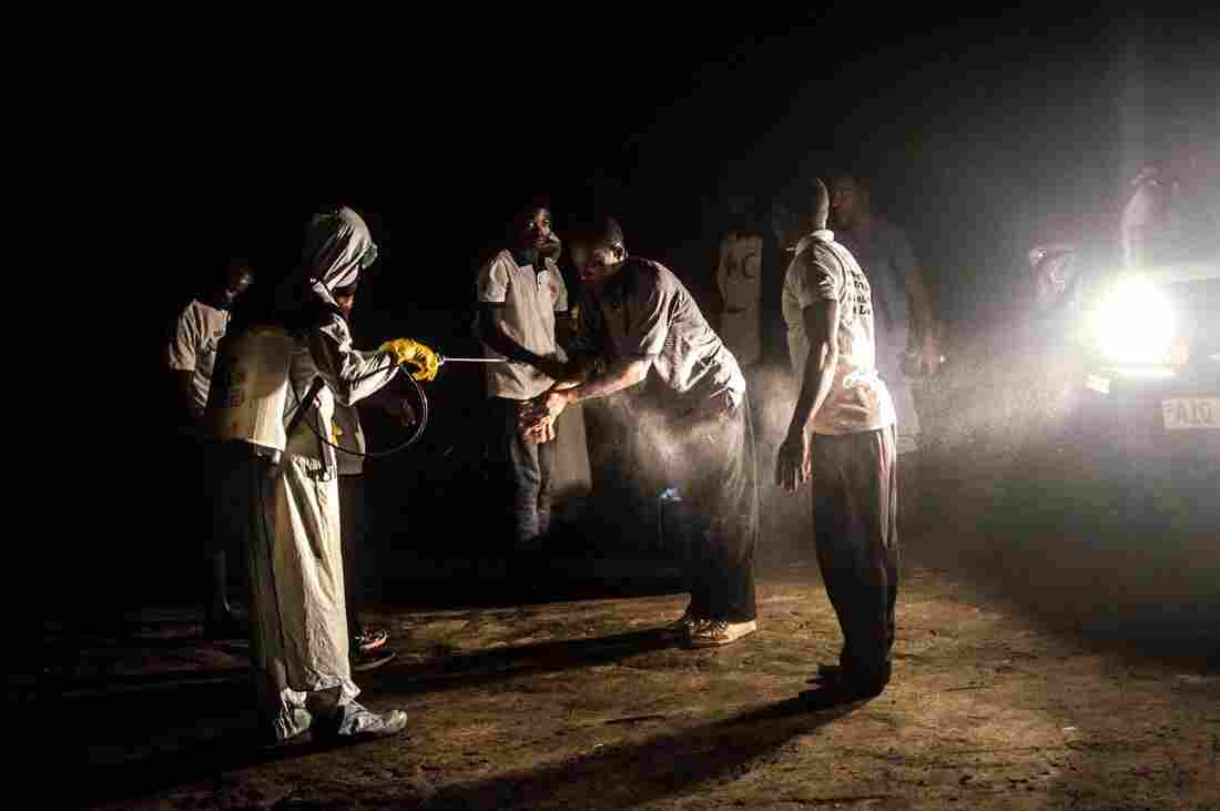 Members of a Red Cross burial team are disinfected after removing the body of an apparent Ebola victim from a home in Pendembu, Sierra Leone.
