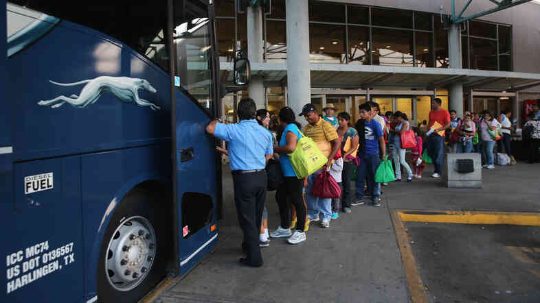"Immigrants board a bus after being released from U.S. Border Patrol detention in Texas last month. An immigration judge says the Obama administration's ""fast-tracking"" effort means many people go into court without an attorney, opening a door to future problems."