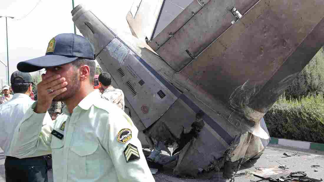 Iranian security forces stand by the wreckage of a plane as they secure the scene of a crash near Tehran's Mehrabad airport Suday.