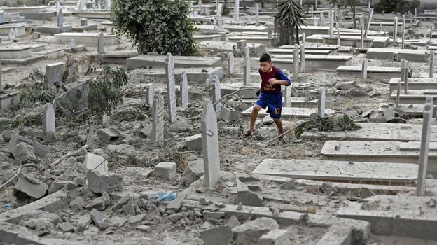 A Palestinian boy runs on the rubble of damaged graves at a cemetery hit by an Israeli strike in Gaza Cita, on Sunday. (AP)