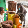 A woman washes her hands before she is allowed to enter a building — part of an Ebola prevention campaign in Freetown, Sierra Leone.