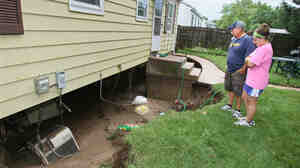 Bob Dobrogowski and his daughter Rosie look at the collapsed basement of his parents' home during July 2010 flooding in Milwaukee.