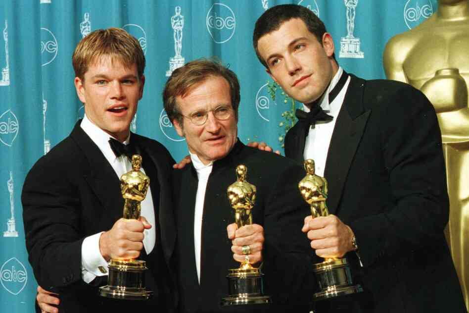 Actor-writers Matt Damon (left) and Ben Affleck pose with Williams holding the Oscars they won for Good Will Hunting at the 70th Annual Academy Awards in 1