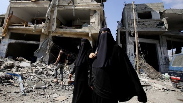 Palestinian women walk past the rubble of their homes in Gaza City's Shijaiyah neighborhood on Monday. An Egyptian-brokered cease-fire halting the Gaza war held into Monday morning, allowing Palestinians to leave homes and shelters as negotiators agreed to resume talks in Cairo. (AP)