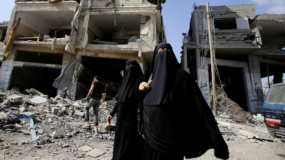 Palestinian women walk past the rubble of their homes in Gaza City's Shijaiyah neighborhood on Monday. An Egyptian-brokered cease-fire halting the Gaza war held into Monday morning, allowing Palestinians to leave homes and shelters as negotiators agreed to resume talks in Cairo.