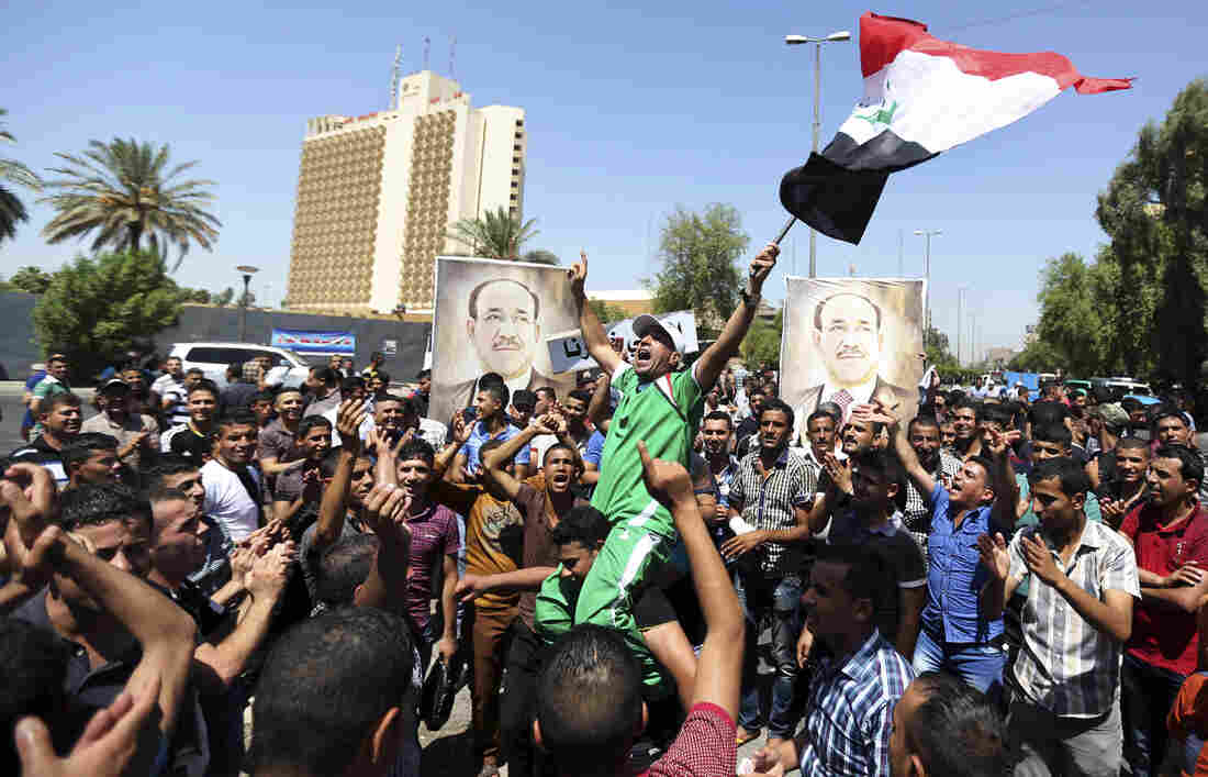 Iraqis chant pro-government slogans and wave flags in a show of support for embattled Prime Minister Nouri al-Maliki during a demonstration in Baghdad Monday. Maliki says he will file a legal complaint against the country's newly elected president.