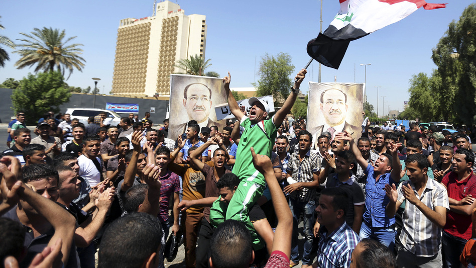 Iraqis chant pro-government slogans and wave flags in a show of support for embattled Prime Minister Nouri al-Maliki during a demonstration in Baghdad Monday. Maliki says he will file a legal complaint against the country's newly elected president. (AP)