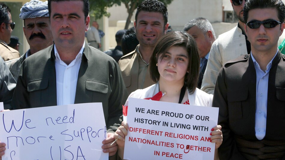 A group consisting mainly of Iraqi Christians hold signs during a rally in front of the U.S. consulate in Erbil, capital of the autonomous Kurdish region of northern Iraq, calling for more support and thanking the US. for air strikes aimed at halting the advance of Sunni Islamic State militants. (AFP/Getty Images)