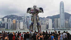 People gather in front of a giant figure of Optimus Prime displayed along the Hong Kong harbor for the world premiere of Transformers: Age of Extinction on June 19.