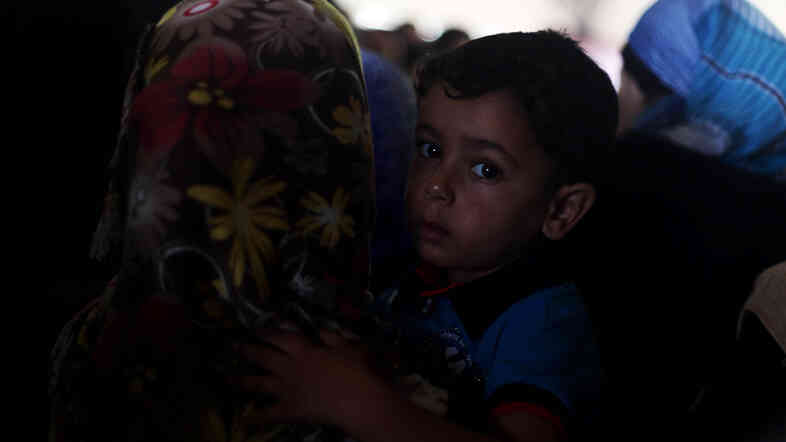 A Palestinian boy, hoping to cross into Egypt with his family, is held by his mother as they wait at the Rafah crossing between Egypt and the southern Gaza Strip on Tuesday. A cease-fire between Israel and Hamas held for a second day Tuesday as officials from both sides held indirect talks in Egypt.