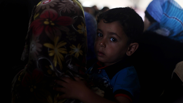 A Palestinian boy, hoping to cross into Egypt with his family, is held by his mother as they wait at the Rafah crossing between Egypt and the southern Gaza Strip on Tuesday. A cease-fire between Israel and Hamas held for a second day Tuesday as officials from both sides held indirect talks in Egypt. (APA /Landov)